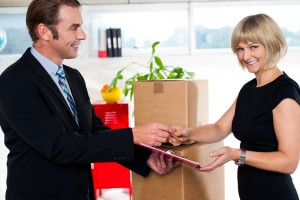 Man handing over business papers of goods delivered in order to get them signed by his casual boss.
